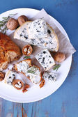 Blue cheese with sprigs of rosemary, bread and nuts on plate and color wooden table background — Stock Photo