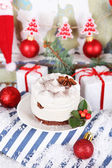 Delicious cake on saucer with holly and berry on Christmas decoration background — Stock Photo