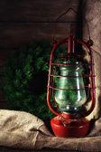Kerosene lamp with wreath on wooden planks background — Stok fotoğraf