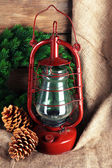 Kerosene lamp with wreath and cones on wooden planks background — Stock fotografie