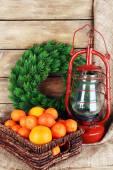 Kerosene lamp with wreath and oranges in wicker basket on wooden planks background — Stok fotoğraf