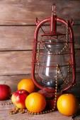 Kerosene lamp with beads and fruits on wooden planks background — Stock Photo
