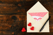 Envelope with hearts and pen on rustic wooden table background — Stock Photo