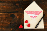Envelope with hearts and pen on rustic wooden table background — ストック写真