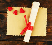 Roll and sheet of paper with hearts on rustic wooden table background — Stock Photo