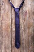 Trendy tie on wooden planks background — Stock Photo