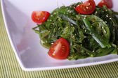 Seaweed salad with slices of cherry tomato on bamboo mat background — Foto de Stock