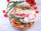 Pangasius fillet with herb, spices and vegetables on cutting board and color wooden table background — Stock Photo