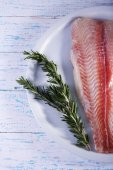 Pangasius fillet with sprigs of rosemary on plate and color wooden table background — Stock Photo