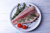 Pangasius fillet with herb and sliced cherry tomatoes on plate and color wooden table background — Stock Photo