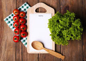 Cutting board with menu sheet of paper, with cherry tomatoes and lettuce on wooden planks background — Stock Photo