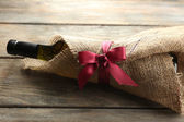 Wine bottle wrapped in burlap cloth on wooden planks background — Stock Photo