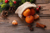 Christmas composition with tangerines on wooden background — Stock Photo