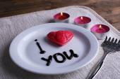 Cookie in form of heart on plate with inscription I Love You, and candles on napkin and wooden table background — Foto de Stock
