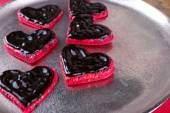 Cookies in form of heart covered chocolate on metal tray background — Stock Photo