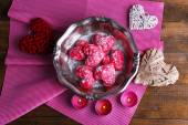 Cookies in form of heart on metal tray with candles and napkins on rustic wooden table background — Stock Photo