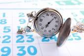 Silver pocket clock on calendar background — Stock Photo