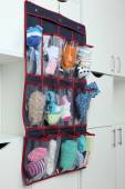 Different socks in hanging bag on closet background — Stock Photo