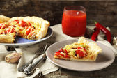 Vegetable pie with paprika, tomatoes and cheese on plate, on wooden background — Stock Photo