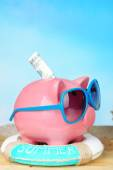 Piggy bank with sunglasses on wooden table, outdoors — Fotografia Stock