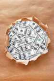 Dollar banknotes through torn  paper — Stock Photo