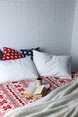 Book and cup on bed — Stock Photo