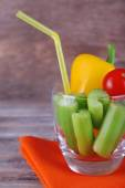 Sticks of celery with sweet pepper and cherry tomato in glass with tube and napkin on rustic wooden background — Foto Stock