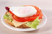 Sandwich with poached egg and vegetables on plate on wooden background — Stock Photo