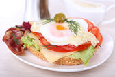 Sandwich with poached egg, tomato and bacon on plate on wooden background — Stock Photo