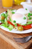 Sandwich with poached eggs, cheese and vegetables on plate on wooden background — Stock Photo