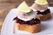 Rye toasts with herring and beets on plate on wooden background — Stock Photo