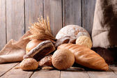Different bread on table on wooden background — Stock Photo