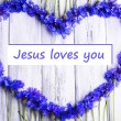 Beautiful cornflowers and text Jesus loves you on wooden background — Stock Photo #63365809