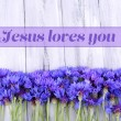 Beautiful cornflowers and text Jesus loves you on wooden background — Stock Photo #63367725