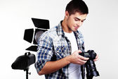 Handsome photographer with camera in photo studio — Stock Photo