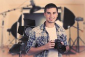 Young photographer with camera on photo studio background — Stockfoto