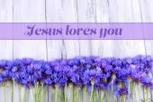 Beautiful cornflowers and text Jesus loves you on wooden background — Stock Photo