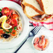 Tasty pasta with shrimps, black olives and tomato sauce on plate on wooden background — Stock Photo #63415011