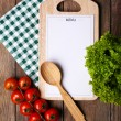 Cutting board with menu sheet of paper, with cherry tomatoes and lettuce on wooden planks background — Stock Photo #63416983