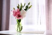 Beautiful flowers in vase with light from window — Stock Photo