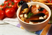 Tasty soup with shrimps, mussels, tomatoes and black olives in bowl on wooden background — Foto Stock