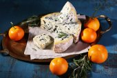 Blue cheese with sprigs of rosemary and oranges on metal tray with sheet of paper and color wooden table background — Stock Photo