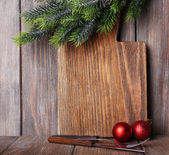 Cutting board with Christmas decoration on wooden planks background — Foto de Stock