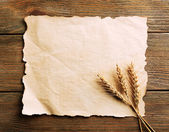 Spikelets of wheat with paper on wooden background — Stock Photo