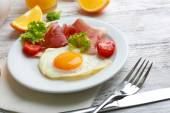 Bacon and eggs on color wooden table background. — Stock Photo