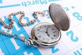 Silver pocket clock on calendar background — Стоковое фото