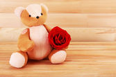Teddy bear with rose on wooden background, love concept — Stock Photo
