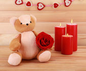 Teddy bear with rose on wooden background, love concept — Stockfoto