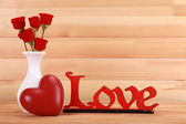 Love concept. Roses and heart on wooden background — Stock Photo