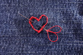 Jeans fabric with red heart embroidered on it, close-up — Stock Photo